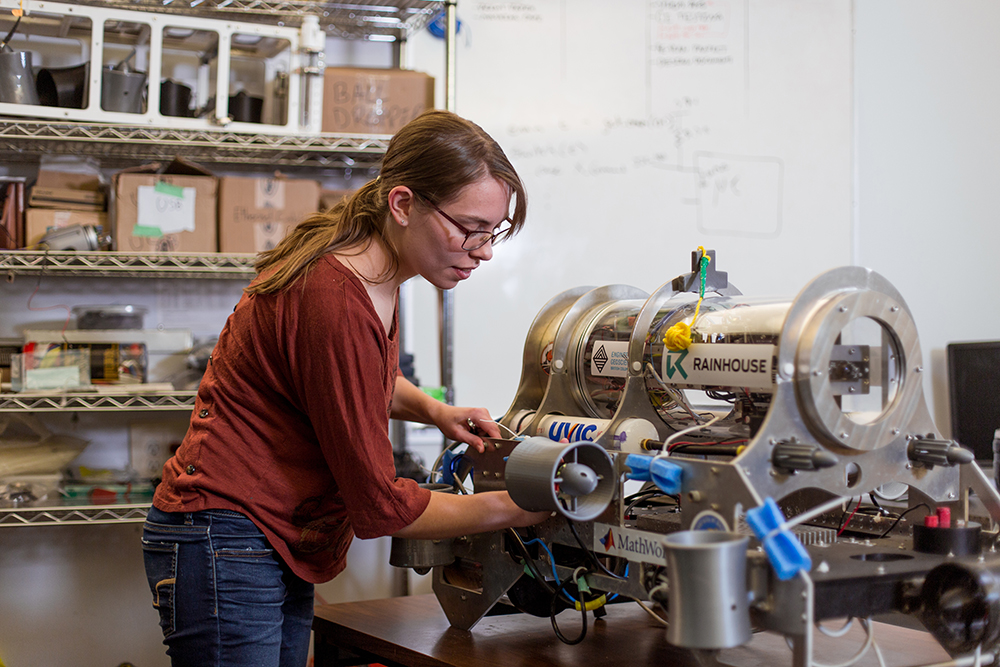 UVic engineering student working on a machine