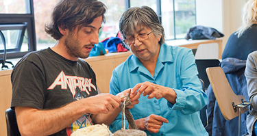 Indigenous Elder teaching UVic Student their culture.